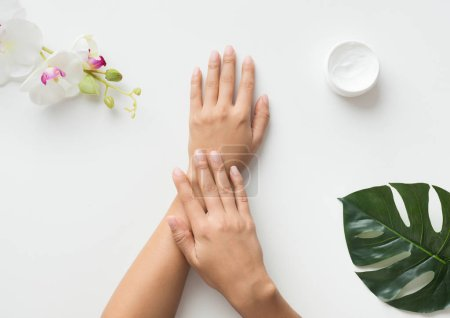 Photo pour Femme mettant de la crème sur ses mains sur fond blanc, vue de dessus - image libre de droit