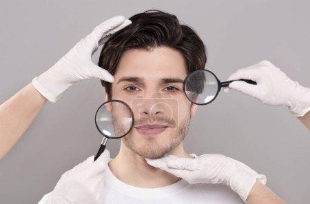 Photo pour Rajeunissement et soins de la peau. Visage du jeune homme beau avec des mains et des magnifiés d'esthéticiennes - image libre de droit