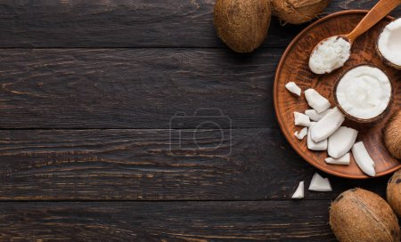 Photo for Chopped coconut, coco pulp on plate and whole coconuts over wooden background, top view, copy space. - Royalty Free Image