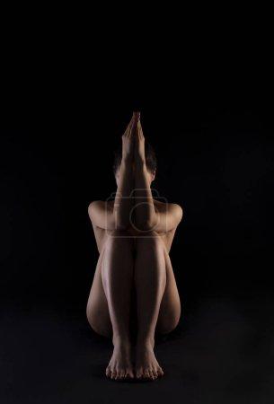 Photo pour Photo art. Silhouette corporelle de femme nue, assise sur fond noir . - image libre de droit