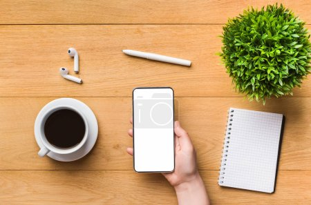 Photo for Cellphone with blank screen in woman hand on workplace with notepad and coffee, mockup, top view - Royalty Free Image