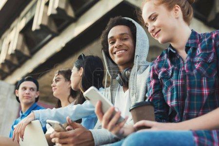 Photo pour Agréable heure d'été. Amis adolescents multiethniques assis à l'extérieur, parlant et utilisant des gadgets, espace libre - image libre de droit