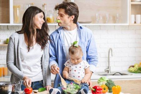 Photo pour Jeunes parents aimants avec leur petit fils cuisinier dans la cuisine . - image libre de droit