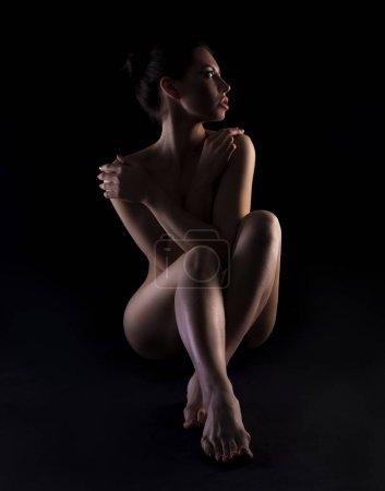 Photo pour Jeune femme nue avec un corps parfait sur fond sombre - image libre de droit