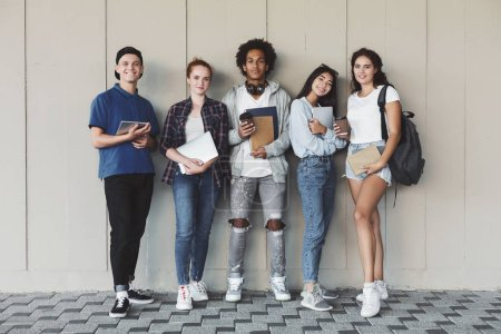 Photo pour Éducation internationale. Heureux étudiants posant avec le personnel d'étude au mur du campus - image libre de droit