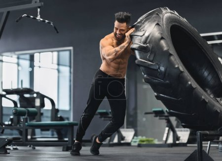 Photo for Crossfit training. Naked man flipping huge tire at gym, free space - Royalty Free Image
