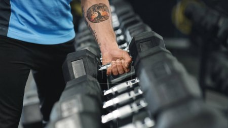 Photo for Closeup shot of muscular male arm picking up heavy dumbbell from equipment rack in modern gym, panorama - Royalty Free Image
