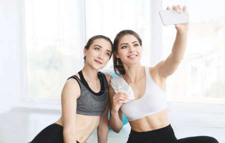 Photo for Charming girlfriends making selfie after yoga class on white background, copy space - Royalty Free Image