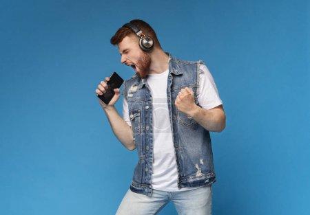 Photo pour Jeune homme aux cheveux roux émotionnel millénaire chantant sa chanson préférée sur smartphone comme microphone sur fond bleu, espace de copie - image libre de droit