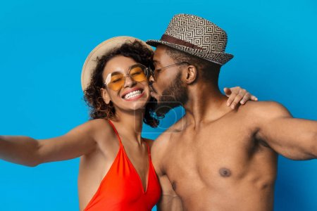 Photo for Love, summer and selfie. Cheerful black couple photographing themselves, guy kissing his girlfriend on camera, blue background - Royalty Free Image