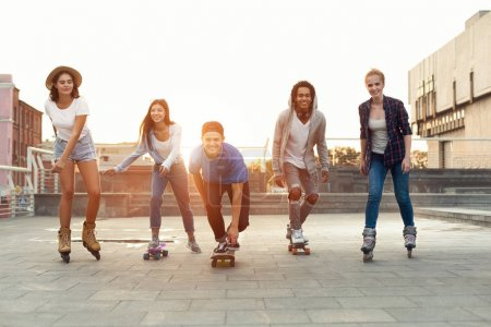 Photo for Summer holidays, vacation and friendship concept. Group of smiling teenagers with roller skates and skateboard riding outdoors on summer evening - Royalty Free Image