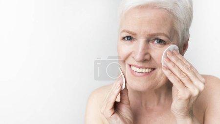 Photo pour Belle femme mature utilisant un coton avec de l'eau micellaire pour démaquiller le visage, fond panoramique léger avec espace libre - image libre de droit