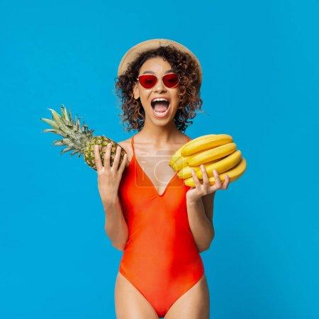 Photo pour Joyeuse femme africaine tenant de l'ananas et des bananes fraîches, fond studio bleu - image libre de droit