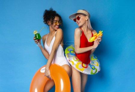 Photo pour Vacances d'été. Diverses petites amies en maillots de bain jouissant d'un cocktail et d'un pistolet à eau, souriant les unes aux autres, fond bleu studio - image libre de droit