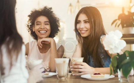 Photo for Young multiracial girls sitting in cafe, drinking coffee with cakes and listening funny life story of their friend - Royalty Free Image