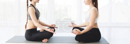 Photo for Two girls in sportswear sitting on black mat and doing yoga opposite each other in studio, crop, panorama - Royalty Free Image