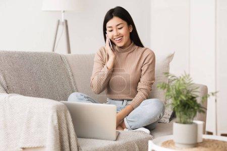 Photo pour Asiatique fille parler sur téléphone et surf Internet sur ordinateur portable, se reposer sur canapé - image libre de droit