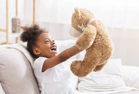 Photo pour Mignon enfant afro-américain étreignant ours en peluche et souriant, petite fille jouant avec jouet préféré à la maison, espace libre - image libre de droit