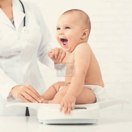 Photo pour Contrôle médical. Adorable bébé assis sur des balances, examen de mesure du poids au bureau du pédiatre, espace libre - image libre de droit