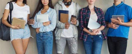 Photo pour Groupe d'étudiants adolescents avec livres, gadgets et sacs à dos, panorama - image libre de droit