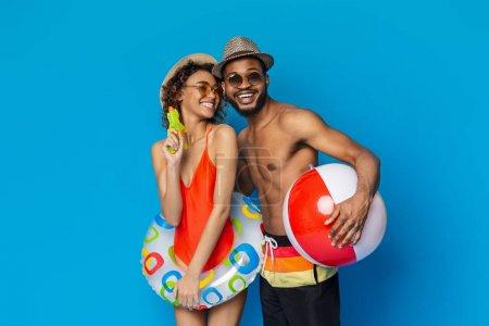 Photo pour Humeur estivale. Couple africain en maillots de bain tenant des jouets de plage, fond studio bleu - image libre de droit