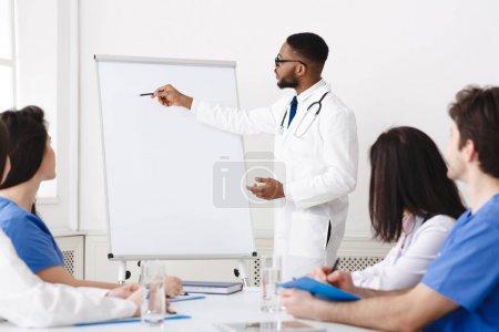 Photo pour Réunion hebdomadaire. Équipe de médecins ayant une séance de remue-méninges dans la salle de conférence - image libre de droit
