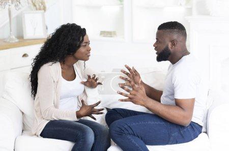 Foto de Hombre y mujer afroamericanos peleando, gesticulando y gritando el uno al otro, sentados en el sofá en casa, espacio libre - Imagen libre de derechos