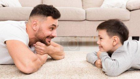 Photo pour Connexion père-fils. Garçon mignon et bel homme se regardant, couché sur le sol à la maison, panorama avec espace vide à l'intérieur - image libre de droit