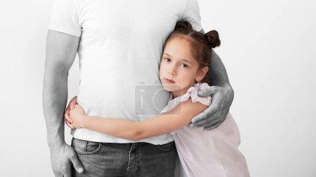 Photo pour Enfant abandonné. Triste fille embrassant la silhouette noire et blanche de son père, portrait en studio, panorama - image libre de droit