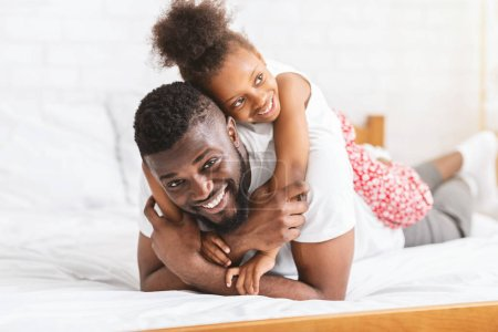 Photo pour Bon week-end familial. Homme afro-américain jouant avec sa petite fille, embrassant sur le lit ensemble, espace libre - image libre de droit