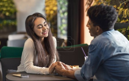 Photo for Black couple teenagers having good time together, holding hands on date in cafe, free space - Royalty Free Image