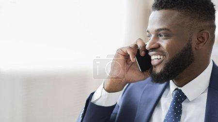 Foto de Conversación de negocios exitosa. Glad hombre de negocios africano hablando en el teléfono celular, mirando el espacio vacío, panorama - Imagen libre de derechos