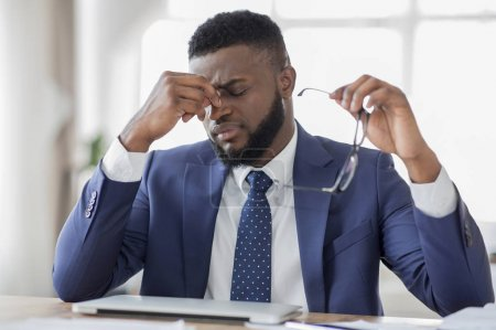 Photo for Feeling sick and tired. Frustrated african businessman massaging his nose and keeping eyes closed, sitting at his working place in office - Royalty Free Image