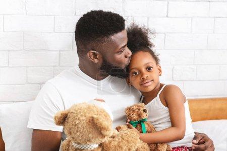 Photo pour Paternité et amour. Soins papa africain embrasser sa petite fille adorable dans le front, jouer ensemble à la maison - image libre de droit