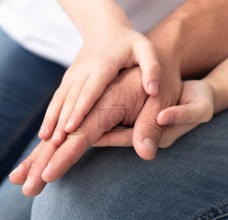 Photo for Family love. Small girl warming her dad hands, close up - Royalty Free Image