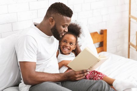 Photo pour Bonne soirée. Homme afro-américain lisant un conte de fées à sa petite fille, assis dans la chambre, espace vide - image libre de droit