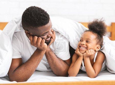 Photo pour L'amour familial. Mignon papa africain et sa fille couchés sur le lit et souriant les uns aux autres, espace libre - image libre de droit