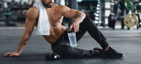 Photo for Little break. Naked man holding water bottle, sitting on floor at gym, panorama - Royalty Free Image