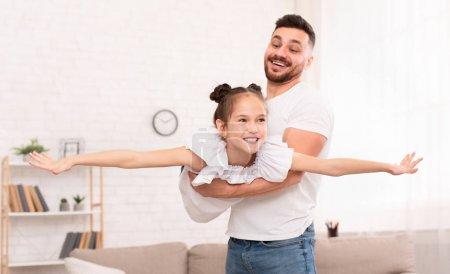 Photo pour Amusant avec papa. Père tenant sa fille mignonne couchée comme un avion, couchée ensemble à la maison, espace vide - image libre de droit