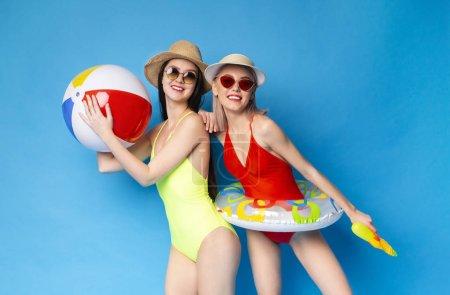 Photo pour Deux femmes millénaires en maillots de bain profitant de vacances d'été avec anneau gonflable, balle et pistolet à eau, fond studio bleu - image libre de droit