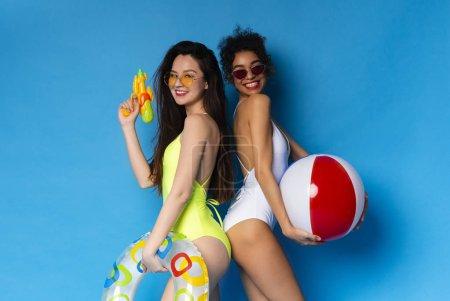 Photo pour Filles millénaires multiethniques profitant de vacances d'été avec des jouets de fête de piscine, fond studio bleu - image libre de droit