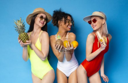 Photo for Summer diet. Healthy diverse girls enjoying fresh sweet fruits, blue studio background - Royalty Free Image