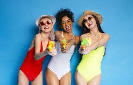 Photo pour Méfiez-vous des femmes millénaires joyeux tirant sur la caméra avec des pistolets à eau et riant sur fond bleu studio - image libre de droit