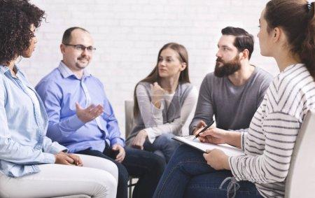 Photo pour Homme parlant avec un psychiatre à une réunion du groupe de désintox, espace libre - image libre de droit