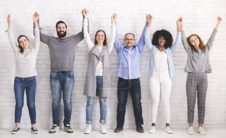 Photo for Group of successful friendly people raising connected hands, white brick wall background - Royalty Free Image
