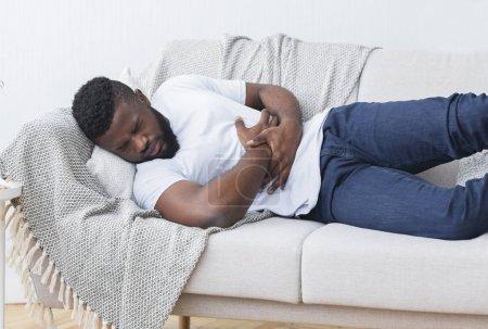 Photo pour J'ai très mal au ventre. Désespéré jeune homme africain étreignant son ventre, souffrant sur le canapé à la maison, espace libre - image libre de droit