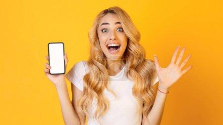 Photo pour Nouvelle application. Femme émotionnelle montrant l'écran vierge de smartphone, regardant l'appareil photo sur fond jaune - image libre de droit