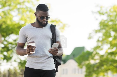 Photo for Pensive african american man using cellphone and drinking coffee to go in the city, panorama, free space - Royalty Free Image