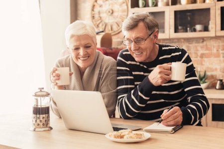 Photo for Cheerful senior couple looking at laptop in kitchen, enjoying coffee, watching movie together - Royalty Free Image