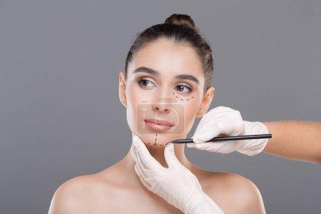 Photo pour Docteur marquage visage jeune femme avant la chirurgie esthétique sur fond gris - image libre de droit